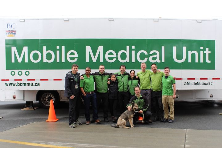 Mobile Medical Unit staff posing in front of MMU logo